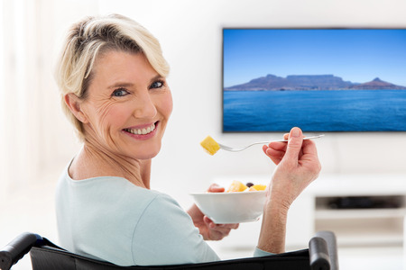 eating salad: happy handicapped elderly woman eating fruit salad at home Stock Photo
