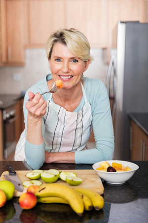 healthy mature woman eating fruit salad at home