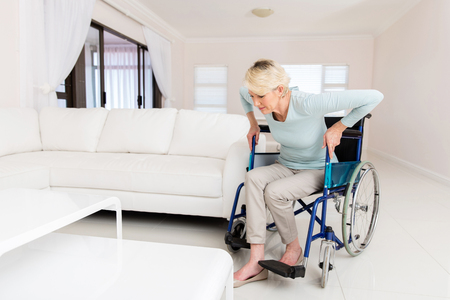 get up: disabled woman trying to get up from wheelchair in living room Stock Photo