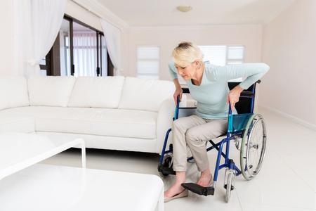 donna disabile cercando di alzarsi dalla sedia a rotelle in salotto