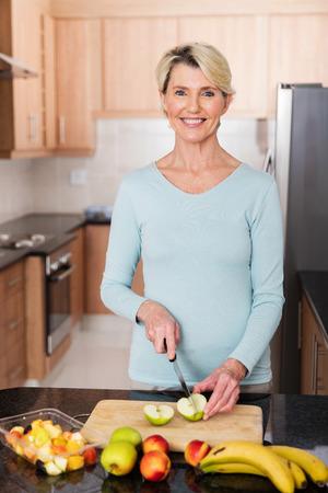 ensalada de frutas: Mujer mayor que hace la ensalada de fruta en la cocina casera