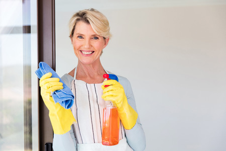 contemporary house: beautiful senior woman cleaning her house