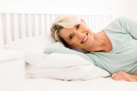 calm woman: happy middle aged woman lying on bed at home