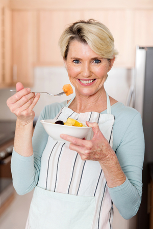 beautiful senior woman eating fruit salad in home kitchen