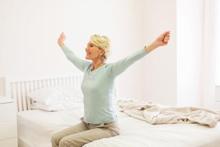 despertarse: feliz mujer de mediana edad levantarse Foto de archivo