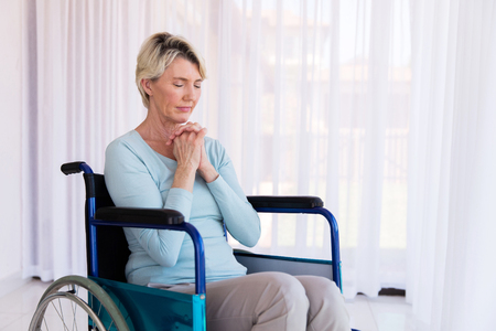 house of prayer: disabled middle aged woman sitting on wheelchair and praying Stock Photo