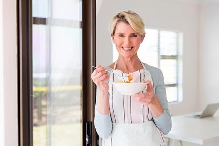 ensalada de frutas: feliz mediados mujer de edad comiendo ensalada de frutas en el hogar