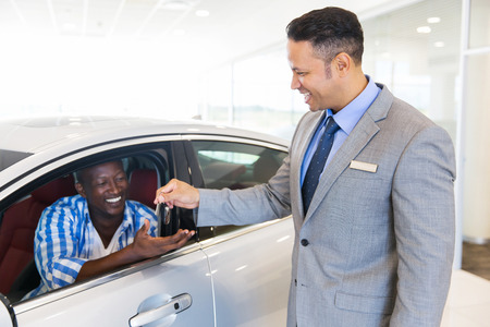 buy car: car salesman handing over new car key to customer sitting inside vehicle at showroom