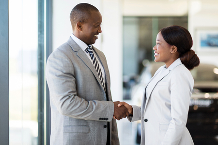 seller: cheerful african car dealer handshake with customer in showroom Stock Photo