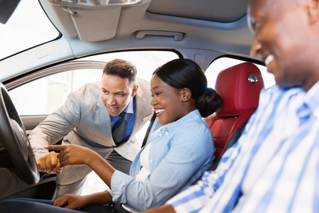 happy customer: salesman showing new car to african couple in showroom