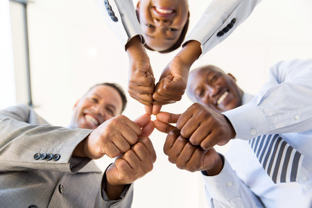 coworkers: underneath view co-workers with thumbs joined together