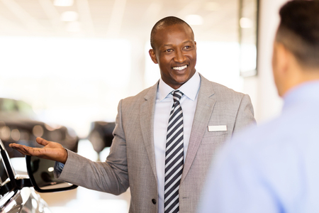 presenting: handsome african salesman presenting new car to clients Stock Photo