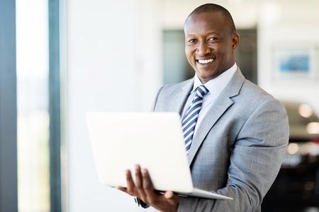 modern afro american vehicle sales consultant using laptop inside showroom Zdjęcie Seryjne