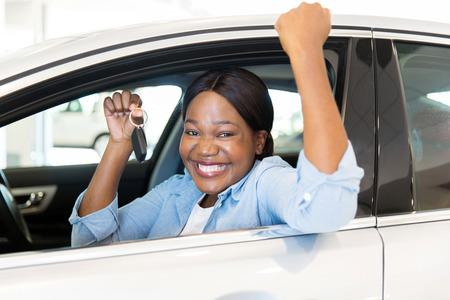 allegro giovane donna africana che mostra la sua nuova chiave di auto concessionaria Archivio Fotografico