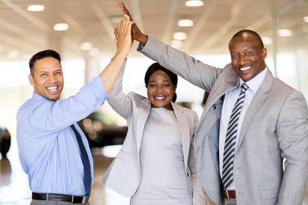 hands high: successful car dealership staff giving high five in showroom