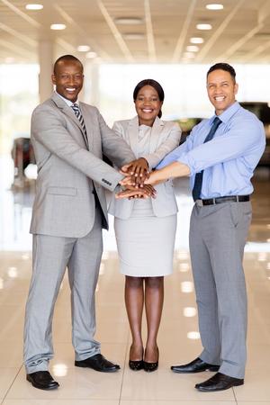 multiracial: multiracial car dealership staff putting their hands together