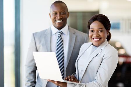 femme africaine: portrait de deux travailleurs avec un ordinateur portable à l'intérieur showroom automobile