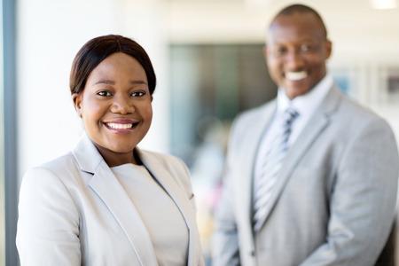 secretaries: hermosa mujer de negocios joven africano de pie delante de su colega Foto de archivo