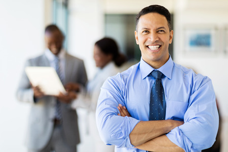 office man: good looking corporate worker in modern office with colleagues on background Stock Photo