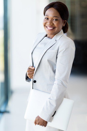 woman business suit: professional afro american businesswoman holding laptop in office