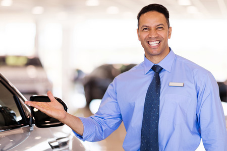 new age: good looking mid age car salesman presenting new cars Stock Photo