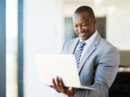 men standing: smart african business man using laptop in office