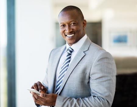 オフィスでスマート フォンを使用してアフリカの笑顔の実業家の肖像画