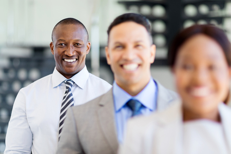 african business: happy african businessman standing in a row with business team Stock Photo