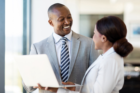 Freundliche afrikanische Fahrzeughändlerhaupt und Verkäuferin arbeitet am Laptop Standard-Bild - 53100646