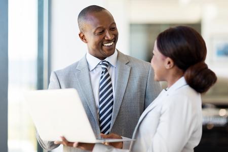 freundliche afrikanische Fahrzeughändlerhaupt und Verkäuferin arbeitet am Laptop