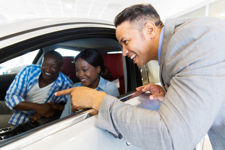 selling service smile: middle aged vehicle salesman showing new car to a happy young couple in showroom Stock Photo