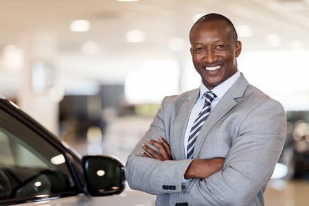 차량 쇼룸에 서있는 아프리카 계 미국인 자동차 판매점 교장