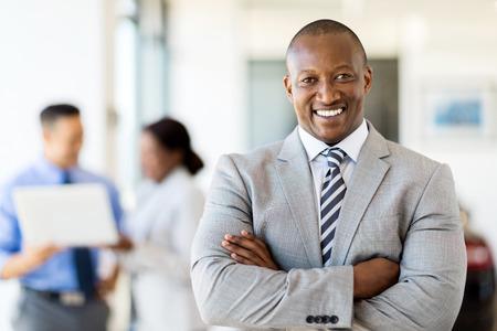 negras africanas: feliz vendedor africano de pie en concesionario de coches con los colegas en el fondo Foto de archivo