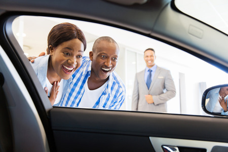 happy african couple choosing luxury car at vehicle dealership looking at the interior