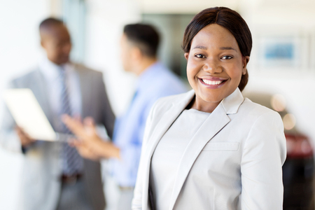 happy african: pretty african american female vehicle sales consultant standing in showroom Stock Photo