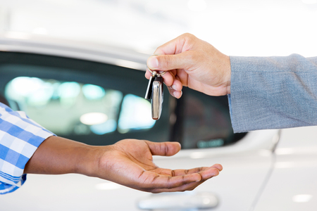 close up of car dealer handing over new car key to customer at showroom Standard-Bild