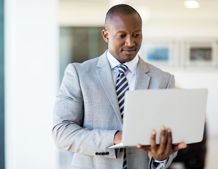successful african entrepreneur working on laptop computer