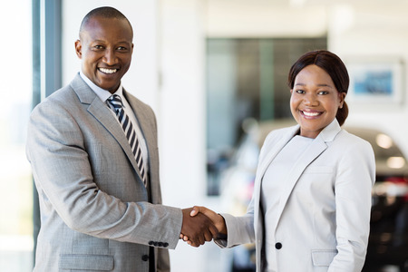 beautiful african woman handshaking with car dealer