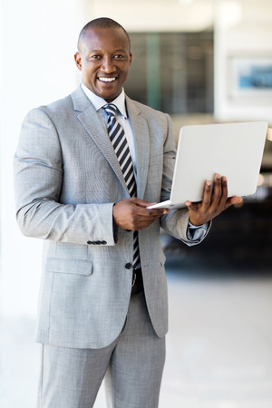 standing businessman: professional african american businessman with laptop Stock Photo