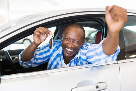 Hombre africano emocionado mostrando una llave del coche dentro de su vehículo nuevo