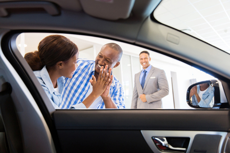 buying: excited african couple at the dealership buying new car