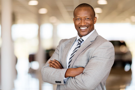 sales occupation: african car sales consultant with arms folded in showroom Stock Photo