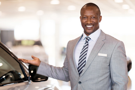 salesman: friendly african car dealer presenting new vehicle in showroom Stock Photo