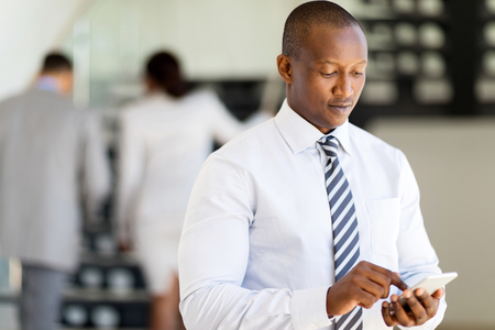 african business man: successful african business man using smart phone Stock Photo
