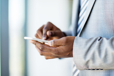 african american man: close up of african businessman hands texting on smart phone
