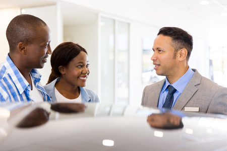 car dealers: young african couple buying new car at dealership