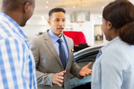 african american woman smiling: middle aged car salesman talking to african couple inside showroom
