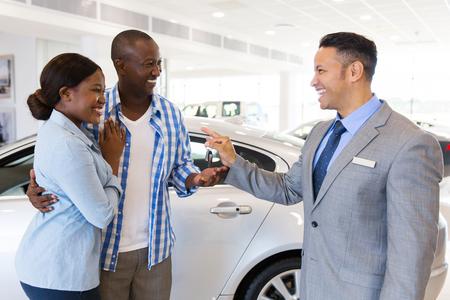 車のショールームでカップルの時代車のセールスマンがアフリカに新しい車のキーを引き渡す半ば 写真素材
