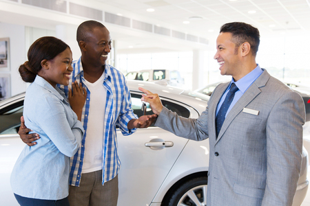 mid age car salesman handing over new car key to african couple in car showroom