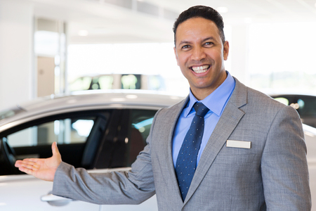 car salesperson: friendly car salesman welcoming gesture at car dealership